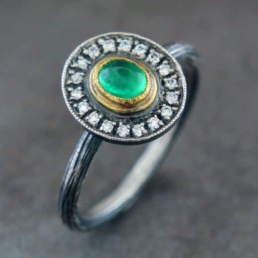antique looking white gold or silver ring with diamonds encircling smooth emerald color stone