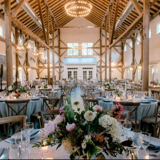 beautifully decorated interior of the light walled Barn at Chapel Hill, set for many tables of guests